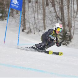 A young adult ski racer is racing down a snow hill. They are wearing a black and yellow ski racing suit, a white helmet, and skis, There are trees in the background.