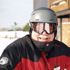 Picture of Pine Knob ski instructor Marty. He is outside standing on the snow, wearing a red and black ski coat and a grey helmet, He is smiling at the camera.