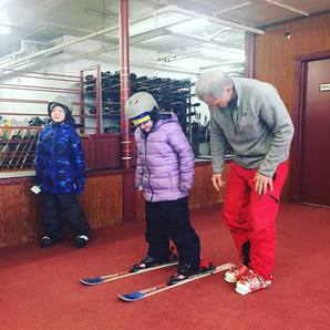 Picture of a Pine Knob Ski Instructor helping a student try on skis and ski boots in the rental area at Pine Knob.