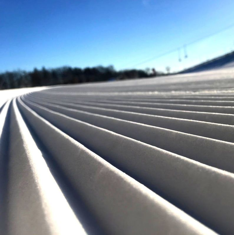 Picture of the freshly groomed snow on the hill at Pine Knob Resort. The sky is blue and the snow is sparkling and white. There are trees off in the background.