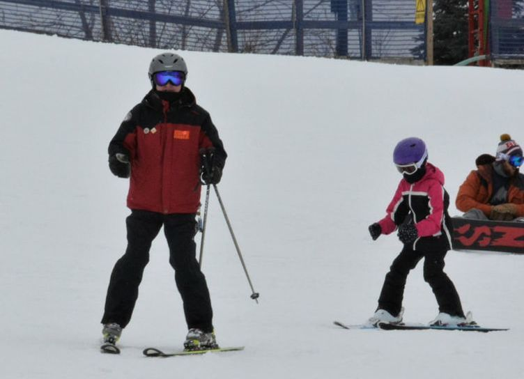 Picture of a Pine Knob ski instructor helping a child to learn to ski on the snowy slopes of Pine Knob.
