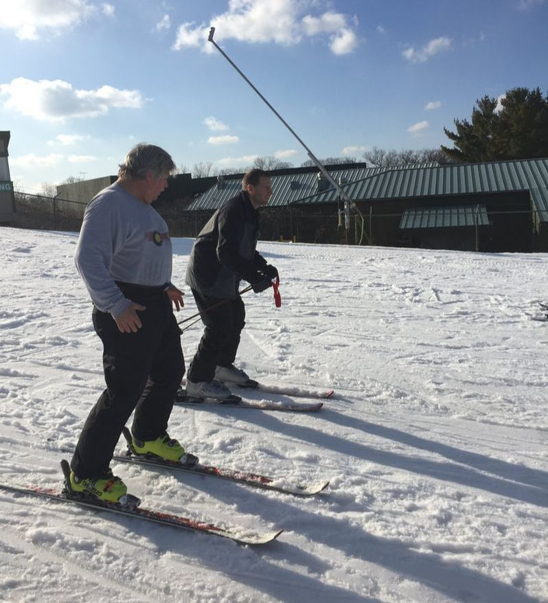 Picture of Pine Knob ski instructor providing a ski lesson to an adult man in the beginner area at Pine Knob.