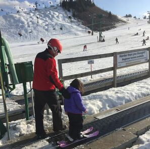 Picture of a Pine Knob Ski Instructor helping a young student on to the beginner lift during a ski lesson.