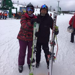 Picture of two adults, one woman and one man. The woman is dressed in colorful ski gear. The man is dressed in black ski gear and he is a coach of the ski race team.