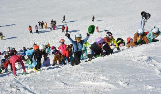 Picture of children climbing a snowy hill during Carnival Day at Pine Knob, They are dressed in colorful winter clothing and having fun running up the snowy slope.
