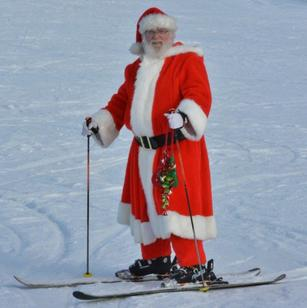 Picture of Santa Claus wearing his red suit. He is skiing on the snowy slopes of Pine Knob.