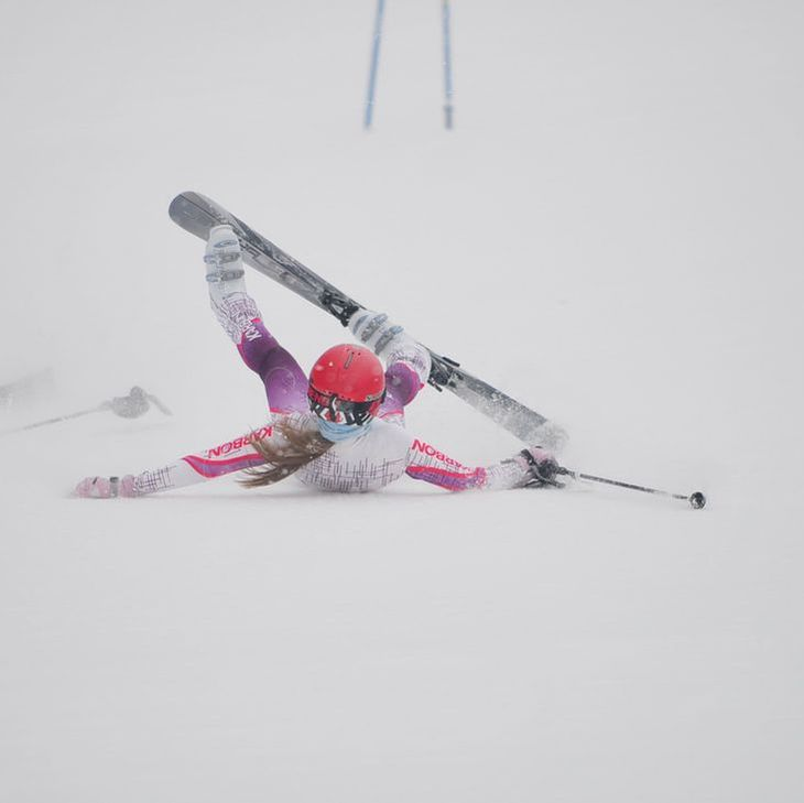 Picture of a young skier in white and purple racing gear who has fallen down in the snow.