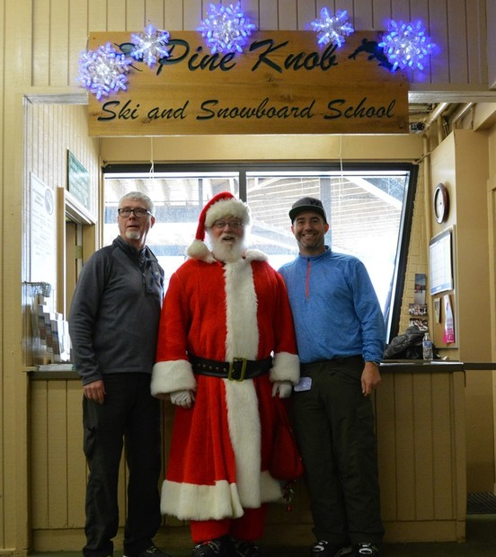 Picture of the Pine Knob Ski School Desk inside the Pine Knob resort lodge. In front of the desk are three people, Pat, Santa Claus, and Jeff King. They are smiling at the camera.