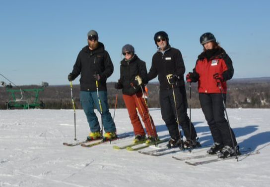 Picture of four Pine Knob ski instructors standing at the top of the snowy hill with their skis on their feet. The sky is blue and it is a nice day.