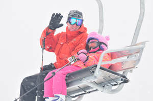 Picture of a man in a red ski coat and black snow pants with a child in a pink snow coat and pants. They are siting together on a chairlift and waving at the camera. They are enjoying a day of skiing.