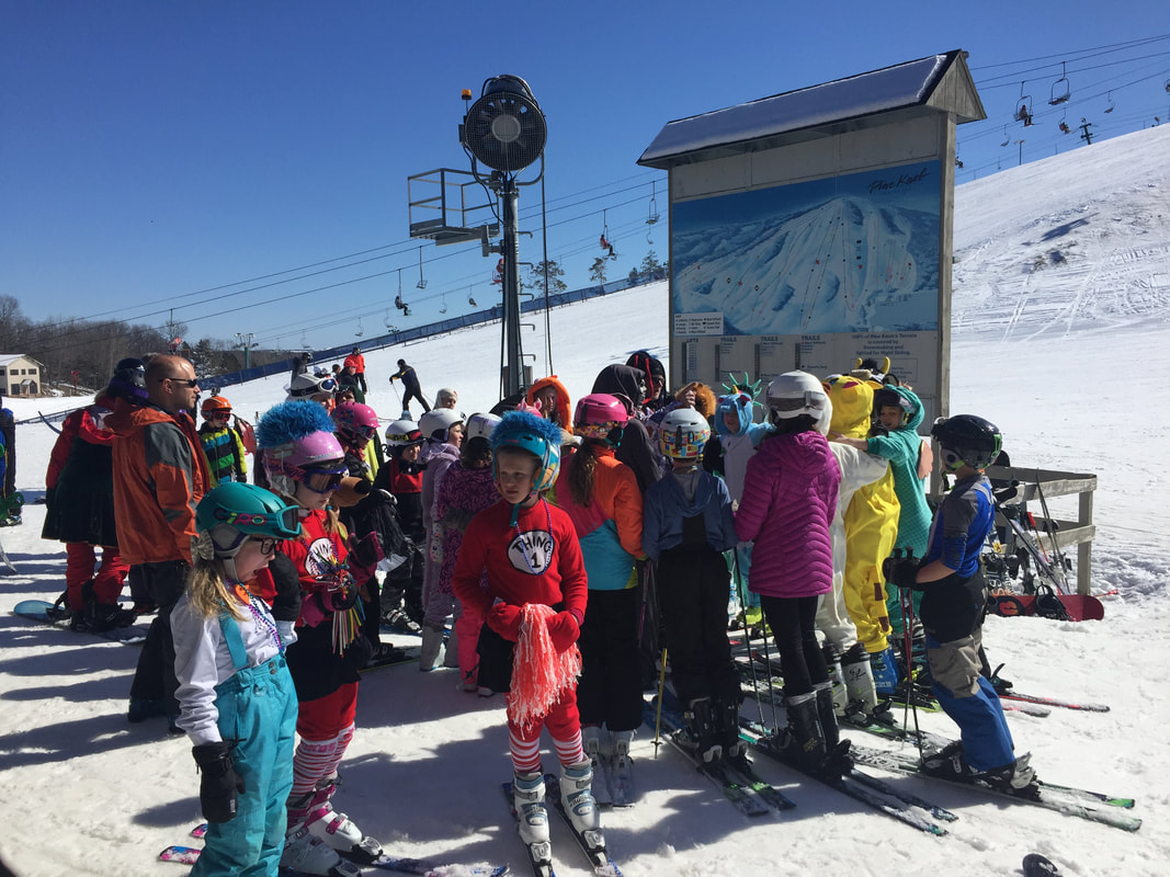 Picture of children and adults at the base of the Pine Knob hill. They are wearing costumes, colorful winter gear, and are celebrating Carnival Day under sunny blue skies.