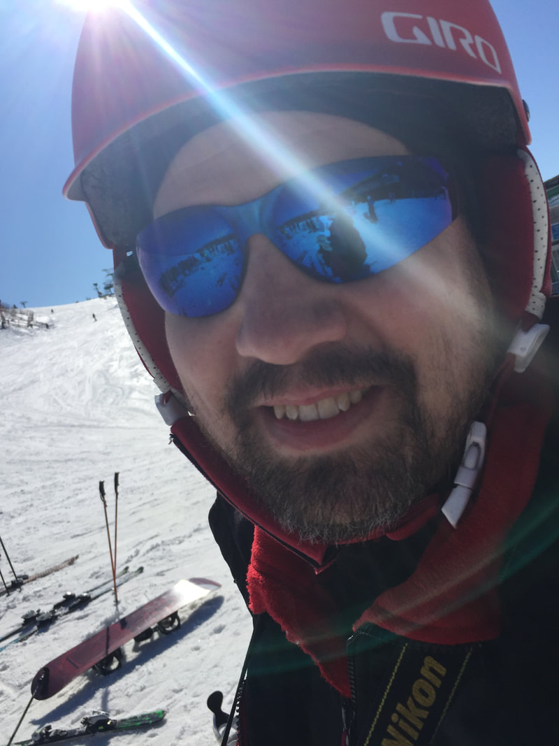 Picture of smiling Pine Knob ski instructor Michael Dwyer. He is wearing his ski gear and is outside on the snowy hill.