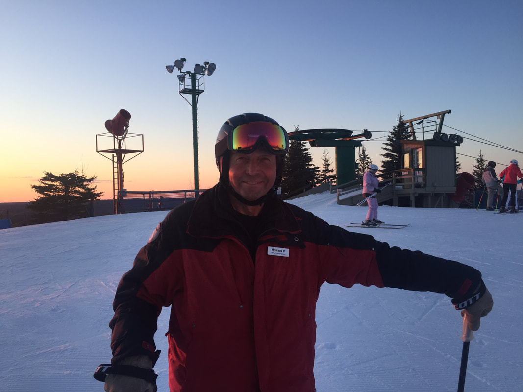 Picture of Howard, Pine Knob ski instructor, standing on the snowy hill at Pine Knob in his skis, smiling at the camera.