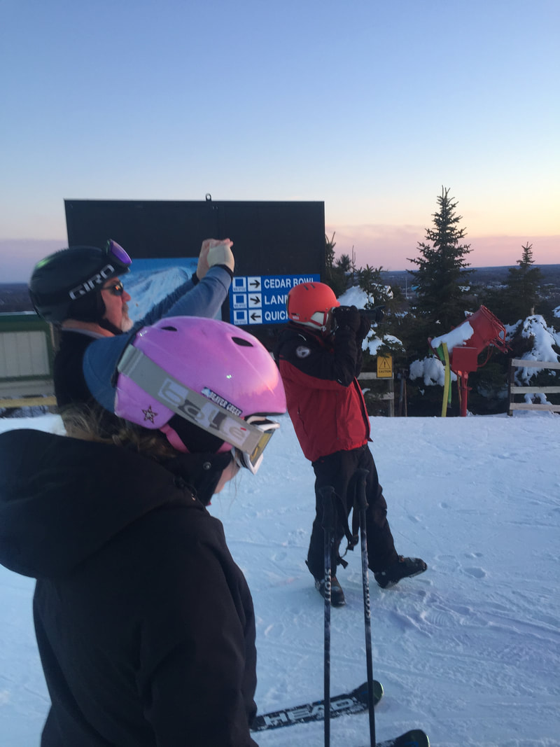 Picture of the Pine Knob Ski and Snowboard instructors standing at the top of the snowy hill, taking pictures of a sunset.