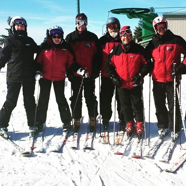 Picture of six Pine Knob ski instructors, wearing red and black winter gear, standing in their skis at the top of the snowy hill at Pine Knob, lined up and smiling at the camera on a beautiful day.
