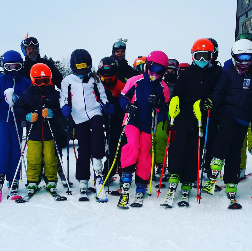 Picture of children dressed in bright colors of coats, snow pants, helmets, and skis. They are outside standing on the snow, posing for the picture. They are part of the race team and their race coaches are standing in the background.