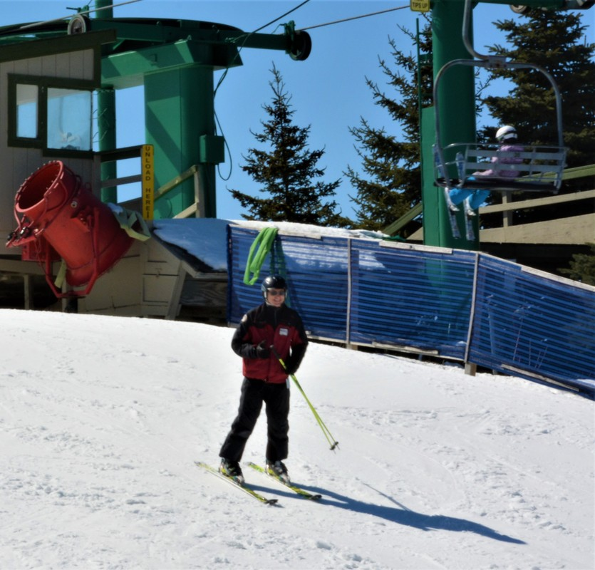 Picture of a Pine Knob ski instructor skiing down the snowy hill at Pine Knob. Behind him is the chairlift, a red snowgun, and some pine trees.