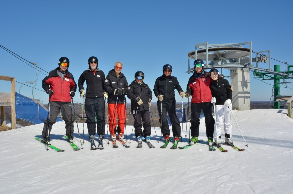 Picture of Pine Knob ski instructors, dressed in all their winter gear and standing in their skis at the top of the Pine Knob hill together, smiling for the camera on a beautiful sunny day.