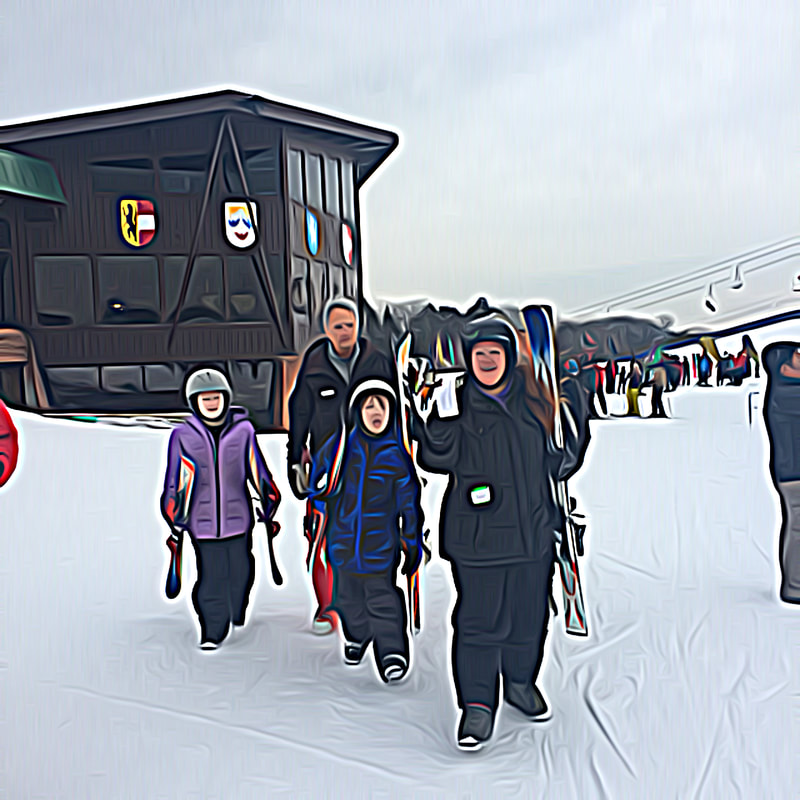 This image is a family of four who are walking from the lodge at Pine Knob out to the beginner area to start their first lesson. They are wearing winter clothing, are carrying skis, and are smiling at the camera.