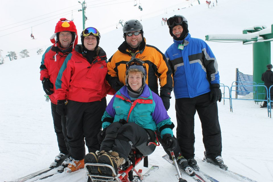 Picture of a group of adults wearing winter gear including colorful coats, snow pants, helmets, and skis. There are four people standing up and one person is sitting in the adaptive ski equipment. They are smiling and enjoying the snow outdoors.