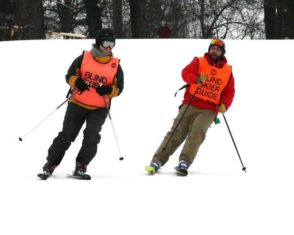 Picture of two skiers at Pine Knob. One is a Blind Skier Guide and the other person is a Blink Skier. They have on vests designating their roles. They also wear winter coats, snow pants, helmets, goggles, and skis. They are skiing on the snow at Pine Knob.