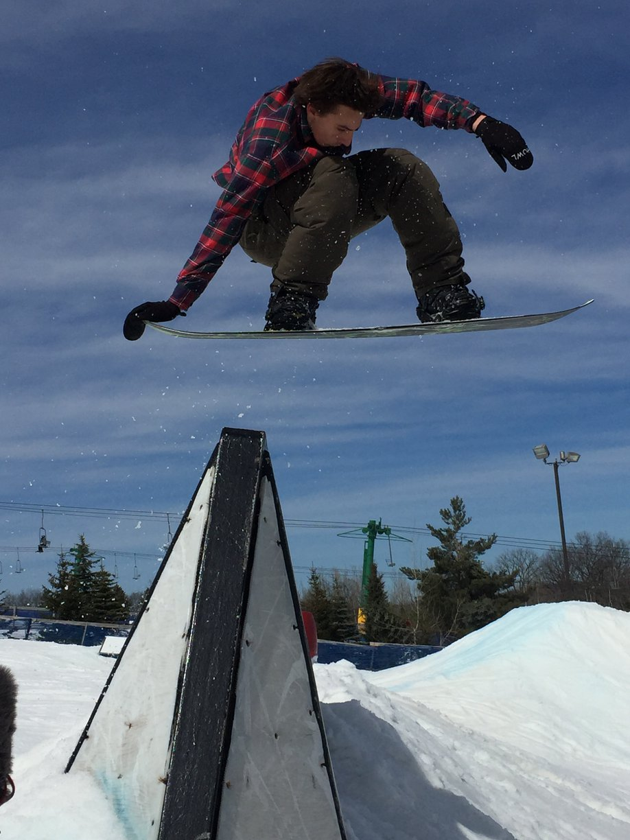 Picture of a snowboarder enjoying the winter snow at Pine Knob, He is wearing a plaid coat and black ski pants and is jumping up in the air on a beautiful winter day.