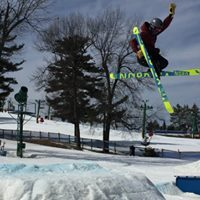 Picture of a skier doing a jump at the Pine Knob terrain park. There is snow and a blue sky,