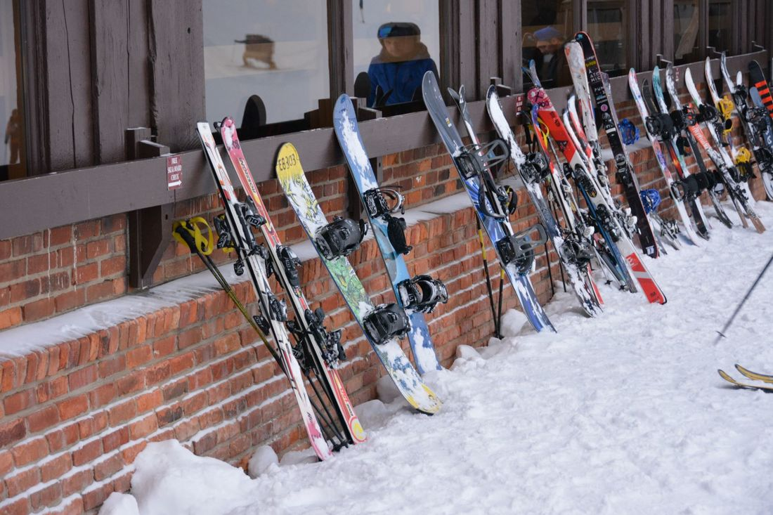 Picture of skis and snowboards lined up along the brick wall beneath the windows of the Pine Knob lodge.