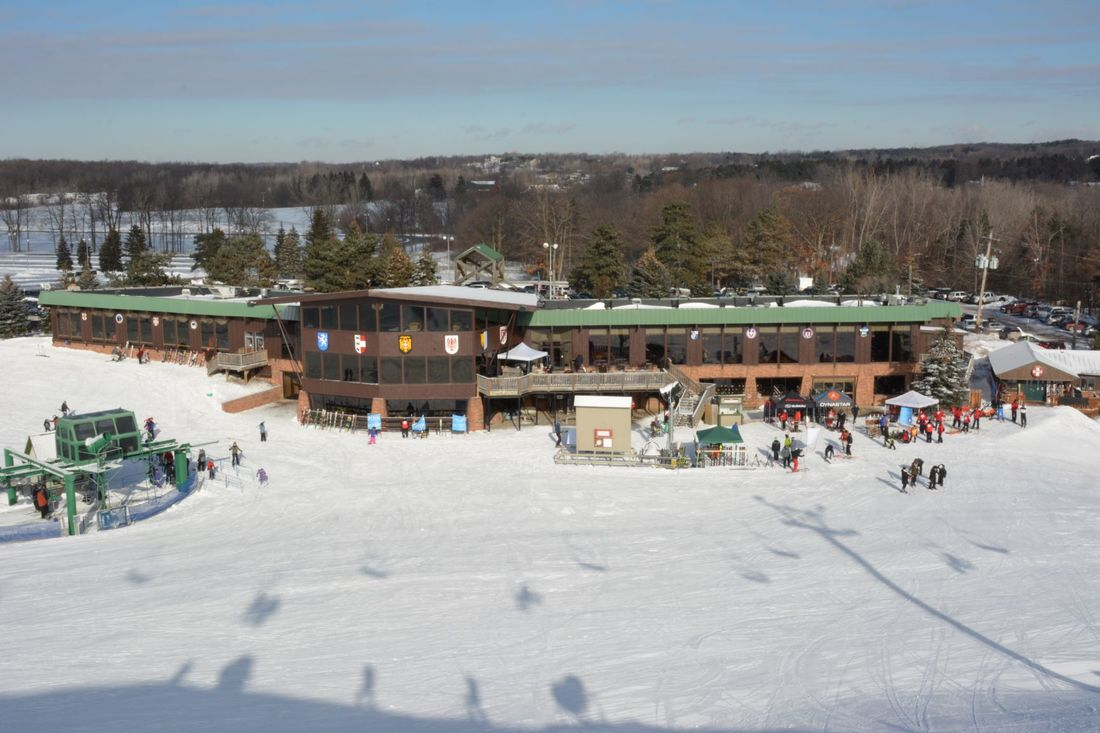 Picture of the Pine Knob Ski Resort lodge. This picture also includes people in and around the building, trees, and the distant scenery as viewed from higher up on the ski hill. The hill is covered in snow and the sky is blue.
