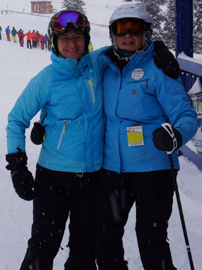 Picture of a man and a woman enjoying skiing together. They are wearing blue coats, black ski pants, and helmets. They are outside, standing on the snow and are smiling at the camera. There are skiers and trees off in the distance behind them.