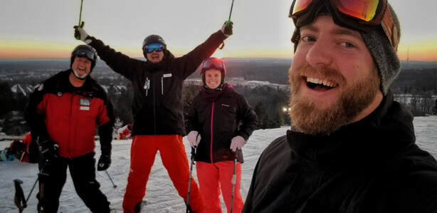 Picture of four Pine Knob Ski and Snowboard instructors standing on top of the Pine Knob Ski Hill. They are smiling, dressed in their winter gear, and there is a soft sunset behind them as they stand on the white snow.