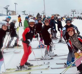 Picture of Coach Tom Lining and his ski racing students. Everyone is outdoor on the snowy hill and bundled up in colorful winter gear including coats, snow pants, helmets, and goggles at Pine Knob.