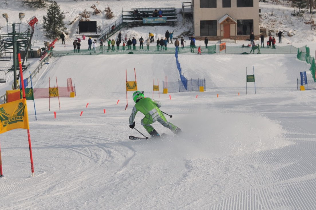 Picture of a ski racer wearing a green racing suit, skiing down the snowy race hill at Pine Knob. At the bottom are spectators and a warming building at Pine Knob.