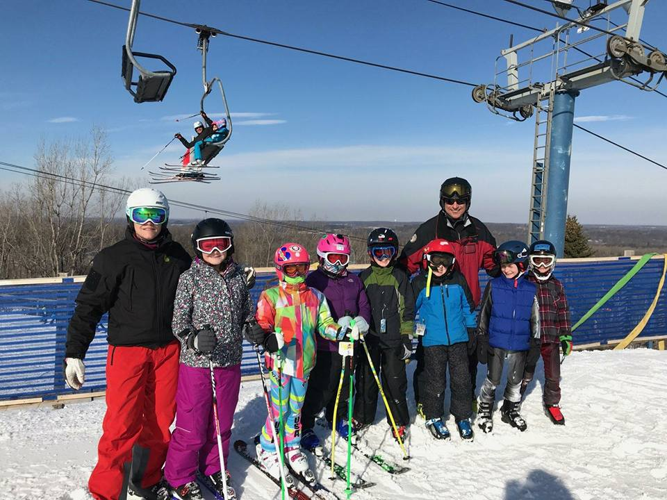 Picture of two Pine Knob Ski Instructors with seven ski racing students. They are a part of the winter race camp that is held after Christmas every year. They are at the top of the race hill at Pine Knob and there is a chairlift overhead transporting people to the top of the hill. They are standing on the snow, smiling at the camera. The sky is blue with a few clouds.